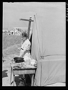 """Mother and family living in tent beside foundation of house which her husband, a defense worker, is building for himself, August 1941."" Photography by John Vachon. Library of Congress, LC-USF34-063666-D (b&w film neg.)."